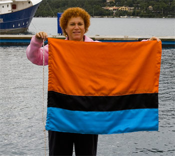 Eve of s/y 'Eve' holding the Chagossian flag which she made