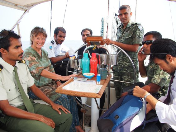 Liz hosts Mr Assad (hidden behind the helm) and various officials. What's the collective noun for a group of Maldivian officials? An efficiency of officials, perhaps?