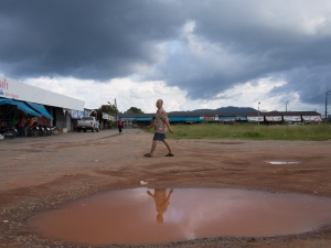 Reflection of a man walking past a puddle with a storm brewing in the background, Satun, Thailand