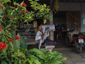 An old man relaxes with a newspaper in Satun, Thailand