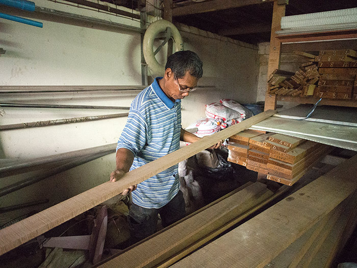 Pong, our head carpenter, inspects and selects some teak planks for the floorboards