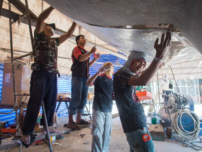 Applying boaxial fibreglass to the hull
