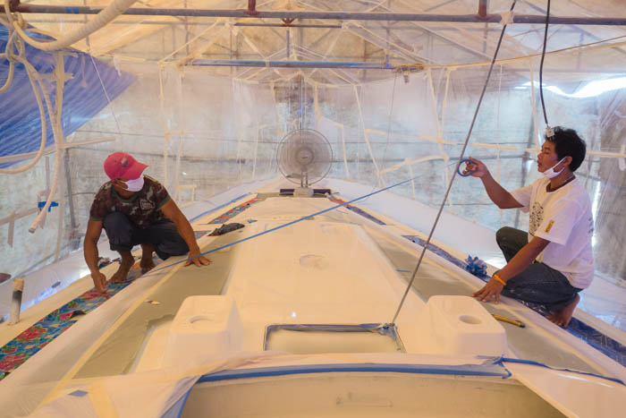 Yodchai and Oot lay the masking for the deck prior to spraying